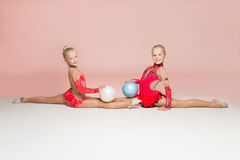Two smiley gymnasts posing with balls royalty free stock images