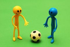 Two smilies playing football. Two smilies playing  football on green pitch Stock Image