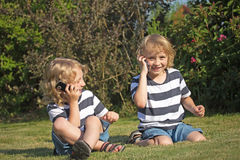 Two smiliing boys are calling outdoors. Two smiling blonde boys are sitting on the lawn and telephone Royalty Free Stock Images