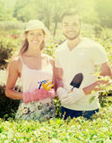 Two smiling adults in flowers garden. At summer day Stock Photo