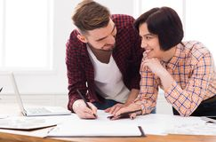 Two smiling architects discussing building plan. Designers team working with new project in office, copy space Royalty Free Stock Photo