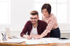 Two smiling architects discussing building plan. Designers team working with new project in office, copy space Royalty Free Stock Images