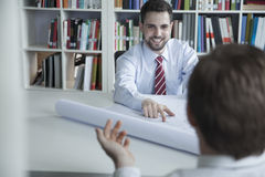 Two smiling architects discussing over a blueprint in the office, Stock Photo