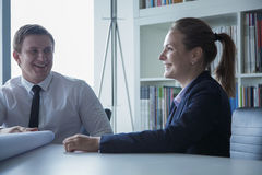 Two smiling architects discussing over a blueprint in the office, Royalty Free Stock Images