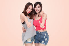 Two smiling asian women giving thumbs up Royalty Free Stock Photo