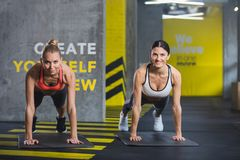 Positive females are doing plank indoors stock images