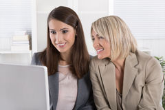 Two smiling attractive businesswoman working in a team looking a Stock Photo