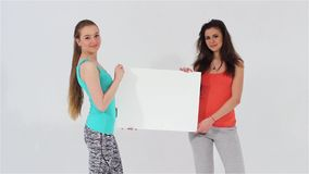 Two smiling attractive girls and shirts holding a white blank banner. Two smiling attractive sports girls walking and looking at camera holding a white blank stock video footage