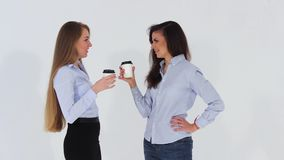 Two smiling attractive office girls in shirts talking and drinking coffee stock footage
