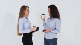 Two smiling attractive office girls talking and drinking coffee stock footage