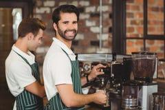 Two smiling baristas preparing coffee Royalty Free Stock Photo