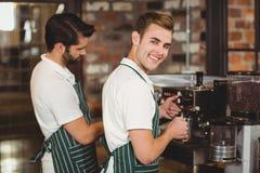 Two smiling baristas preparing coffee Stock Images