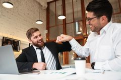 Two smiling bearded colleagues in formalwear punched while sitti. Ng at office Royalty Free Stock Photos