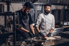 Two smiling bearded cooks dressed in uniforms preparing sushi in the kitchen.