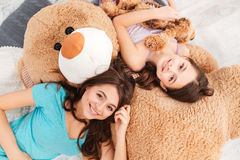 Two smiling beautiful sisters lying on big soft plush bear Stock Photography