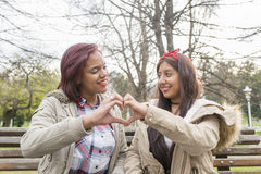 Two smiling beautiful woman showing heart with their fingers. Royalty Free Stock Photos