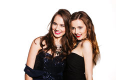 Two smiling beautiful women in cocktail dresses. Two beautiful women in elegant black cocktail dresses celebrating  isolated on white Royalty Free Stock Photos
