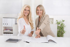 Two smiling blond businesswoman working in a team recommend fina Stock Images