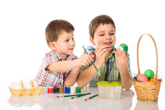 Two smiling boys painting easter eggs together Royalty Free Stock Image