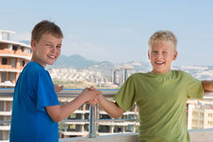 Two smiling boys in T-shirts are shake hands Royalty Free Stock Image