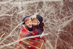 Two smiling brothers hugging each other covered with a warm blanket on a winter day. Two brothers hugging each other covered with a warm blanket on a winter day royalty free stock image