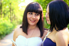 Two smiling brunette women reading a book in a summer park Stock Photos