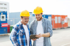 Two smiling builders in hardhats with tablet pc. Business, building, construction, technology and people concept - two smiling builders in hardhats looking at stock images