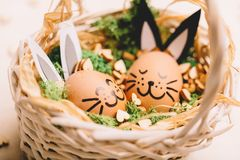Two smiling egg-bunnies laying in the basket. Two smiling bunnies laying in the basket with grass and wooden hearts. Easter egg Stock Photos