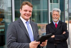 Two smiling  business men with a tablet Stock Image