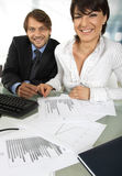 Two smiling business people. Business couple is smiling at camera while making an analyses Stock Images