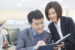 Two Smiling Business People Looking Down at Note Pad and Working Together Stock Photo