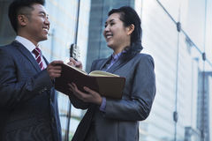 Two smiling business people outside meeting and writing in personal organizer Royalty Free Stock Photos