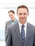 Two smiling business people posing in a row. At work stock photos