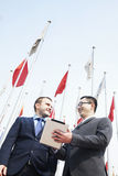 Two smiling business people talking and holding digital tablet Stock Photo