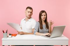 Two smiling business woman man colleagues sit work at white desk with contemporary laptop isolated on pastel pink background. stock photography