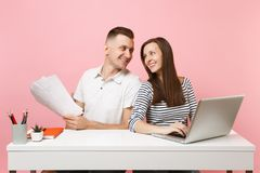 Two smiling business woman man colleagues sit work at white desk with contemporary laptop on pastel pink background. royalty free stock photos