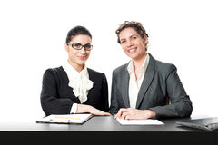 Two smiling business women sitting at front desk Stock Photos