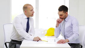 Two smiling businessmen or architects in office. Business, architecture and office concept - two smiling businessmen or architects with blueprint in office stock footage