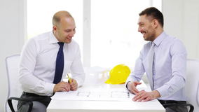 Two smiling businessmen or architects in office. Business, architecture and office concept - two smiling businessmen or architects with blueprint in office stock video