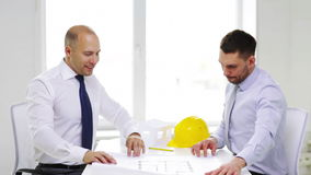 Two smiling businessmen or architects in office. Business, architecture and office concept - two smiling businessmen or architects with blueprint in office stock video footage