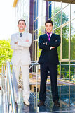 Two smiling businessmen. With arms crossed standing on the building background Stock Photography