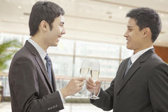 Two smiling businessmen celebrating and toasting champagne flutes, indoors Stock Image