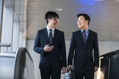 Two smiling businessmen coming up the escalator together Stock Photography