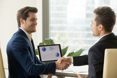 Two smiling businessmen handshaking, partners satisfied with fin royalty free stock photo