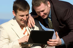 Two smiling businessmen with laptop. Two young smiling businessmen watch at laptop stock photos