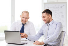 Two smiling businessmen with laptop in office. Business, technology and office concept - two smiling businessmen with laptop in office Stock Photo