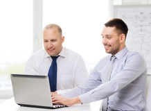 Two smiling businessmen with laptop in office. Business, technology and office concept - two smiling businessmen with laptop in office Stock Image