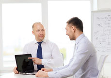 Two smiling businessmen with laptop in office. Business, technology and office concept - two smiling businessmen with laptop having presentation in office Royalty Free Stock Photography