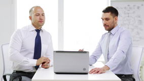 Two smiling businessmen with laptop in office stock video footage