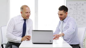 Two smiling businessmen with laptop in office stock footage